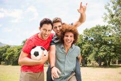 Amis heureux en parc avec le football Images libres de droits