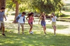 Amis heureux en parc avec le football Image libre de droits