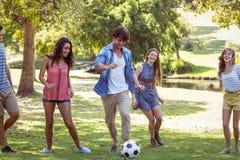 Amis heureux en parc avec le football Photos stock