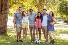Amis heureux en parc avec le football Image stock