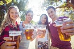 Amis heureux en parc ayant des bières Image stock