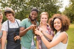 Amis heureux en parc ayant le barbecue Image stock