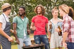Amis heureux en parc ayant le barbecue Photographie stock
