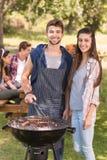 Amis heureux en parc ayant le barbecue Image libre de droits