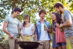 Amis heureux en parc ayant le barbecue Photos stock