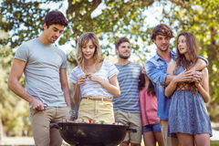 Amis heureux en parc ayant le barbecue Images stock
