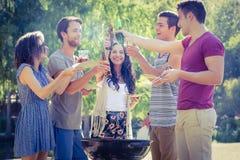 Amis heureux en parc ayant le barbecue Images libres de droits