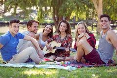 Amis heureux en parc ayant le pique-nique Photographie stock libre de droits