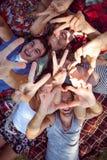 Amis heureux en parc ayant le pique-nique Images stock