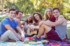 Amis heureux en parc ayant le pique-nique Photos stock
