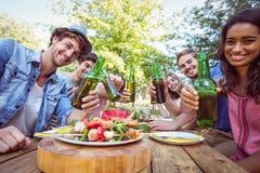 Amis heureux en parc ayant le pique-nique Image stock
