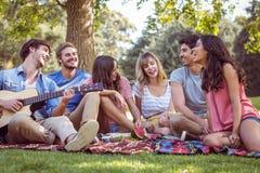 amis heureux en parc ayant un pique-nique Photos stock