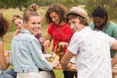 Amis heureux en parc prenant le déjeuner Photographie stock libre de droits