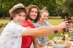 Amis heureux en parc prenant le déjeuner Photo stock