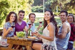 Amis heureux en parc prenant le déjeuner Photos libres de droits