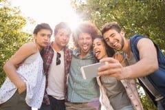 Amis heureux en parc prenant le selfie Photographie stock