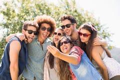 Amis heureux en parc prenant le selfie Photos stock
