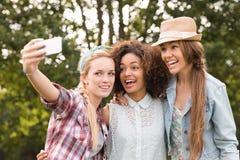 Amis heureux en parc prenant le selfie Image libre de droits