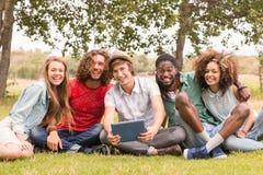 Amis heureux en parc regardant le comprimé Photo libre de droits