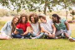 Amis heureux en parc regardant le comprimé Image stock
