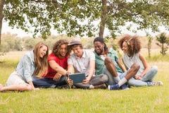 Amis heureux en parc regardant le comprimé Images stock