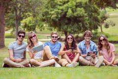 Amis heureux en parc regardant le comprimé Image libre de droits