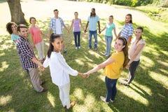 Amis heureux en parc tenant des mains Image stock