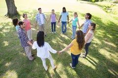 Amis heureux en parc tenant des mains Images stock