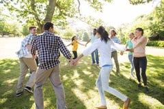 Amis heureux en parc tenant des mains Photographie stock