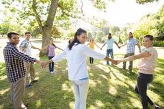 Amis heureux en parc tenant des mains Image libre de droits