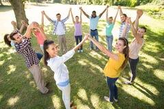 Amis heureux en parc tenant des mains Photos libres de droits