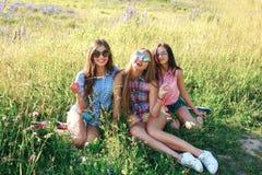 Amis heureux en parc un jour ensoleillé Le portrait de mode de vie d'été de trois femmes de hippie apprécient le beau jour, porta Photographie stock