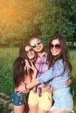 Amis heureux en parc un jour ensoleillé Le portrait de mode de vie d'été de trois femmes de hippie apprécient le beau jour, porta Photographie stock libre de droits