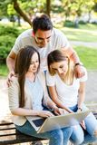 Amis heureux en parc utilisant l'ordinateur portable et apprécier de ther le jour Images stock
