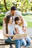 Amis heureux en parc utilisant l'ordinateur portable et apprécier de ther le jour Image libre de droits