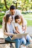 Amis heureux en parc utilisant l'ordinateur portable et apprécier le jour Photo stock