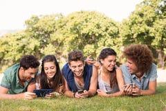 Amis heureux en parc utilisant leurs téléphones Photo stock
