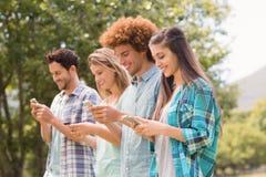 Amis heureux en parc utilisant leurs téléphones Photo libre de droits