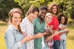 Amis heureux en parc utilisant leurs téléphones Image libre de droits
