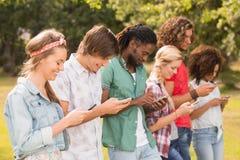 Amis heureux en parc utilisant leurs téléphones Image stock