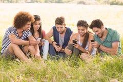 Amis heureux en parc utilisant leurs téléphones Photos stock