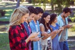 Amis heureux en parc utilisant leurs téléphones Photos libres de droits