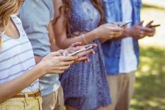 Amis heureux en parc utilisant leurs téléphones Images libres de droits