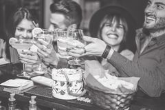 Amis heureux encourageant avec le cockatil dans une barre de cru - les jeunes ayant l'amusement grillant des verres de cocktails  images libres de droits