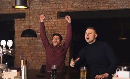 Amis heureux encourageant pour l'équipe préférée dans le bar Images stock