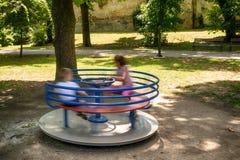 Amis heureux, enfants ayant l'amusement sur le rond point au terrain de jeu Photos stock