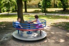 Amis heureux, enfants ayant l'amusement sur le rond point au terrain de jeu Photo stock