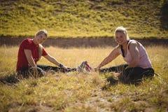 Amis heureux exécutant étirant l'exercice pendant le parcours du combattant Image stock