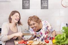 Amis heureux faisant cuire dans la cuisine Photographie stock