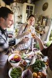 Amis heureux faisant cuire ensemble dans la cuisine photographie stock libre de droits